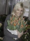 Hembra rubia que sostiene tulipanes Fotos de archivo