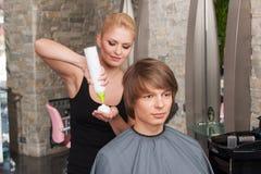 Blonde Herrenfriseurfrau mit Haarkremeisspray Stockfotos