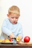 Blonde het jonge geitjekleuter van het jongenskind met scherpe het fruitappel van het keukenmes Royalty-vrije Stock Afbeelding