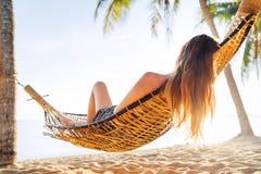 Blonde het longhaired vrouw ontspannen in hangmat scharnierend tussen palmen op het zandstrand royalty-vrije stock foto
