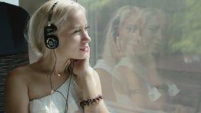 Blonde het luisteren muziek in hoofdtelefoons in de trein stock video