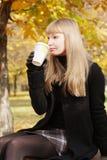 Blonde in het zwarte drinken van kop Royalty-vrije Stock Afbeelding
