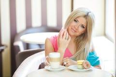 Blonde heureuse à une table dans un café Photos libres de droits