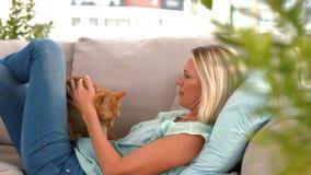 Blonde heureuse avec le chat d'animal familier sur le sofa clips vidéos