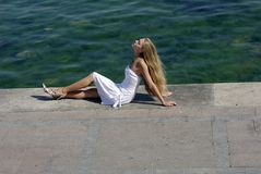 Blonde heureuse en mer proche blanche sur la jetée Image stock