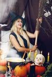 Blonde Hexe mit einem Besen, abgetönt Stockbild