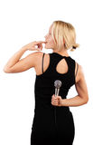 Blonde hiding microphone Stock Photo