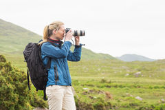 Blonde on a hike taking a photo Royalty Free Stock Images