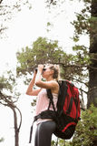 Blonde hiker looking through binoculars. In the nature Stock Photos