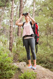 Blonde hiker looking through binoculars. In the nature Royalty Free Stock Photo