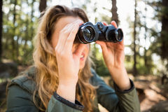 Blonde hiker looking through binoculars. In the nature Royalty Free Stock Photos