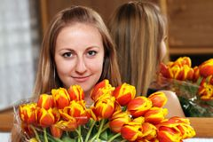Blonde holding bunch of flowers Royalty Free Stock Images