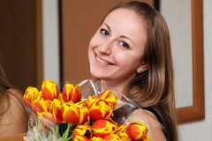 Blonde holding bunch of flowers Royalty Free Stock Photos