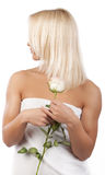 Blonde holding a flower and looking Stock Photo