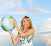 Blonde holding globe. Blonde in field on green grass holding globe in hand under blue sky(heaven Stock Photography