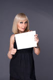 Blonde holding in hands of white blank. Blonde holding itself in hands of white sheet of paper Stock Photography