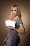 Blonde holding in hands of white blank. Blonde holding itself in hands of white sheet of paper Stock Photos