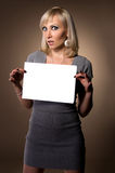 Blonde holding in hands of white blank. Blonde holding itself in hands of white sheet of paper Stock Photo