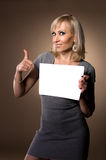 Blonde holding in hands of white blank. Blonde holding itself in hands of white sheet of paper Stock Image
