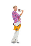 Blonde holding paint brush wearing a tool belt Royalty Free Stock Photo