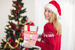 Blonde holding pile of gifts in front of the christmas tree Stock Photo