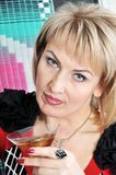 The blonde holds a drink with ice. Royalty Free Stock Photography