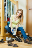 Blonde housewife cleaning shoes Royalty Free Stock Images