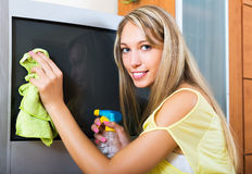 Blonde housewife cleaning TV Royalty Free Stock Image