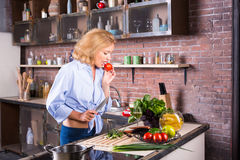 Blonde housewife lick taste tomato on kitchen stock images