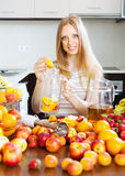 Blonde housewife making beverage with fruits Royalty Free Stock Images