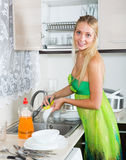 Blonde housewife washing plates Royalty Free Stock Images