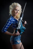 Blonde with industrial hammer. dark background. Royalty Free Stock Photos