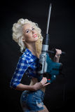 Blonde with industrial hammer. dark background. Royalty Free Stock Photography