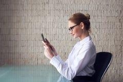 Blonde intelligente Geschäftsfrau, die an Tablette arbeitet Lizenzfreies Stockfoto