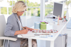 Blonde interior designer working on her desk Stock Photography