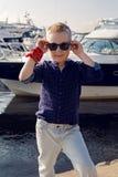 Blonde 8 Jahre des Babys in einem blauen Hemd, helle Hose Lizenzfreies Stockbild
