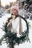 Blonde jonge dame met Kerstmiskroon in de winterbos Royalty-vrije Stock Fotografie