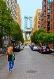 Blonde jonge vrouw die met achtergrond van de Brug van Manhattan en bakstenen muur oude gebouwen en architectuur in Brooklyn in S royalty-vrije stock foto