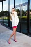 Blonde jonge vrouw in roze kleding en het witte laag stellen Royalty-vrije Stock Afbeeldingen