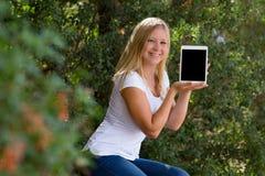 Blonde jonge vrouwen die digitale tablet tonen openlucht Royalty-vrije Stock Afbeeldingen