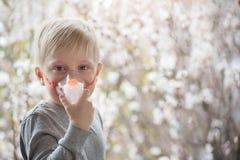 Blonde jongen in de ademhaling van maskerinhaleertoestel op een achtergrond van bloeiende bomen De behandeling van het huis preve stock foto