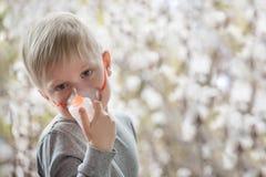Blonde jongen in de ademhaling van maskerinhaleertoestel op een achtergrond van bloeiende bomen De behandeling van het huis preve royalty-vrije stock afbeelding