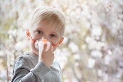 Blonde jongen in de ademhaling van maskerinhaleertoestel op een achtergrond van bloeiende bomen De behandeling van het huis preve royalty-vrije stock foto's