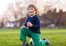 Blonde jongen van speelvoetbal 4 met voetbal op voetbalgebied Royalty-vrije Stock Afbeelding