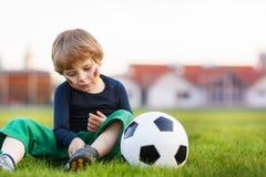 Blonde jongen van speelvoetbal 4 met voetbal op voetbalgebied Stock Afbeelding
