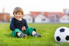 Blonde jongen van speelvoetbal 4 met voetbal op voetbalgebied Stock Afbeeldingen