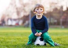 Blonde jongen van speelvoetbal 4 met voetbal op voetbalgebied Royalty-vrije Stock Fotografie