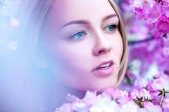 Blonde joven adorable en flores rosadas florecientes Imágenes de archivo libres de regalías