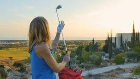 Blonde joven alegre con el club de golf almacen de metraje de vídeo