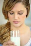 Blonde joven con el vidrio de leche Imágenes de archivo libres de regalías